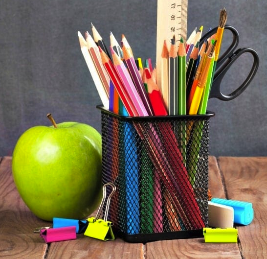A wire pencil holder and a green apple on a desk. Items in the pencil holder include colored pencils, scissors, paint brushes, and a wooden ruler. Items on the desk include colorful binder clips and erasers.