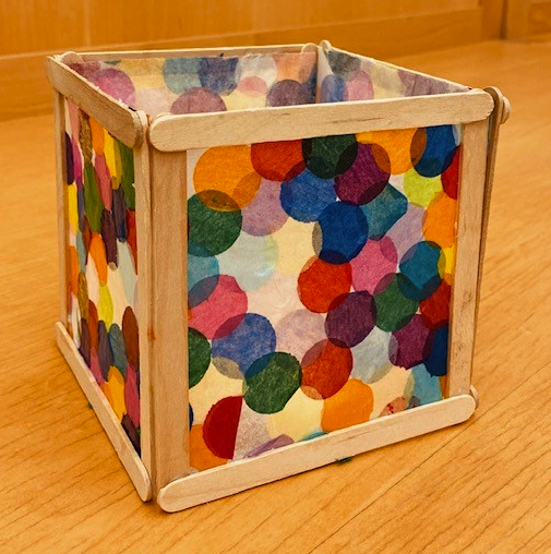 A paper lantern craft. Popsicle sticks form the box frame of a colorful paper lantern. The paper sides are patterned with overlapping colorful circles.