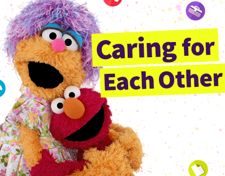 Sesame Workshop: Caring for Each Other. Muppets Mae and Elmo smiling and hugging. Mae has purple hair and is wearing a flower printed dress. Elmo has red fur.